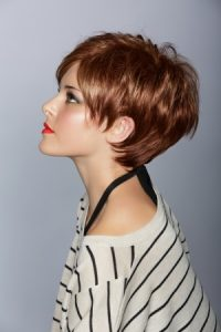 14692501 - profile of a beautiful woman with red lips and short feathered red hair in modern bob over studio background