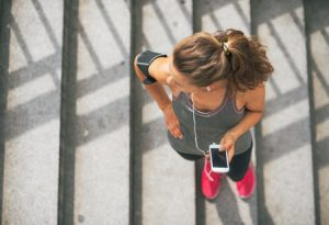 31723849 - portrait of fitness young woman with cell phone outdoors in the city