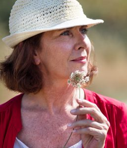 46940898 - wellbeing in countryside - closeup of gorgeous mature woman with summer hat thinking,alone with field flower in hands,natural summer daylight