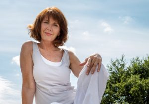 46956921 - senior zen - smiling, beautifully aging woman sitting on a stone for outdoors yoga session wearing white seeking serenity and wellness in a park,summer daylight