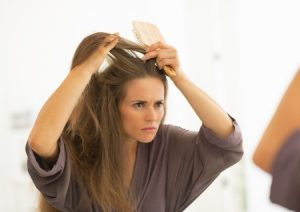 27700356 - concerned young woman combing hair in bathroom