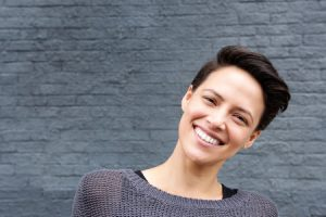 51673374 - close up portrait of a smiling young woman with short hair against gray background