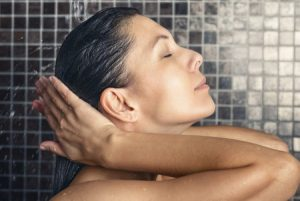 35647316 - attractive woman washing her hair in the shower rinsing it off under the spray of water with her head tilted back and eyes closed in a hair care, beauty and hygiene concept