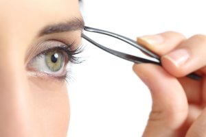 25191646 - close up of a woman eye and a hand plucking eyebrows isolated on a white background