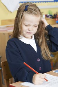 60748625 - female elementary pupil suffering from head lice in classroom
