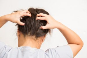 57261728 - woman suffering from an headache itching her head