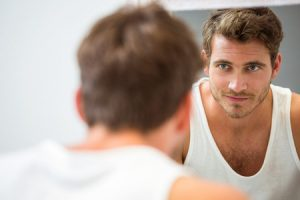54646827 - smart young man looking at himself in mirror at bathroom