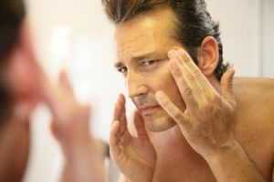 34768675 - middle-aged man in bathroom applying facial lotion